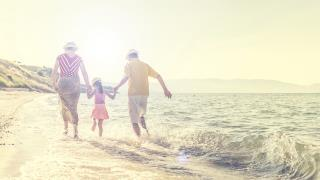 family walking by the ocean