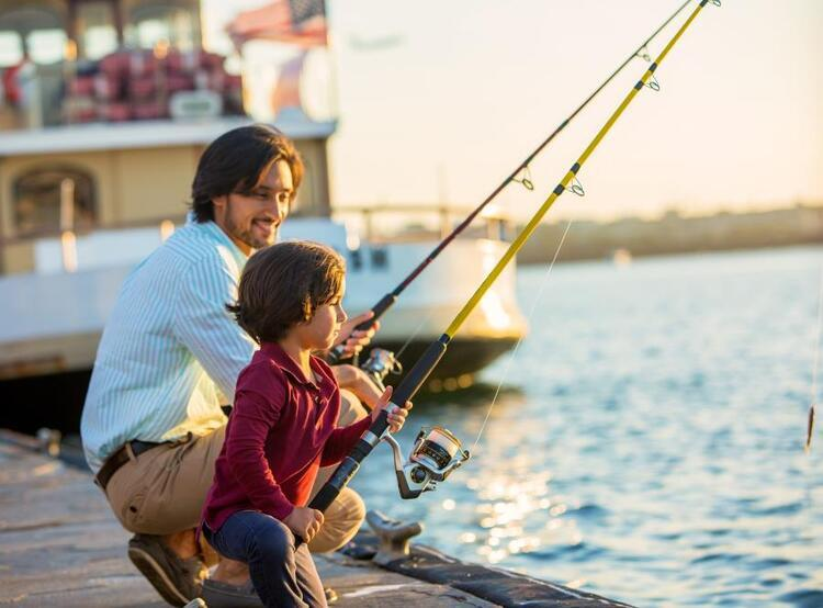 man and son fishing on dock
