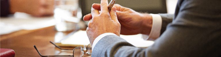 business people's arms and hands at a conference table